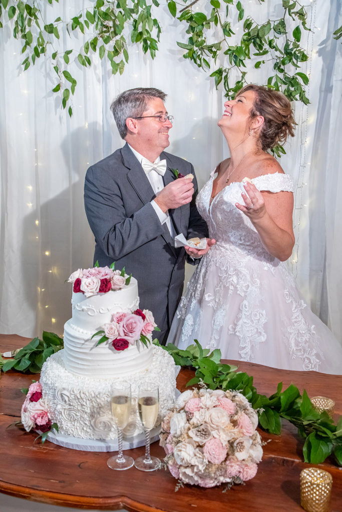 Cherie and Mark feed each other wedding cake at the reception.