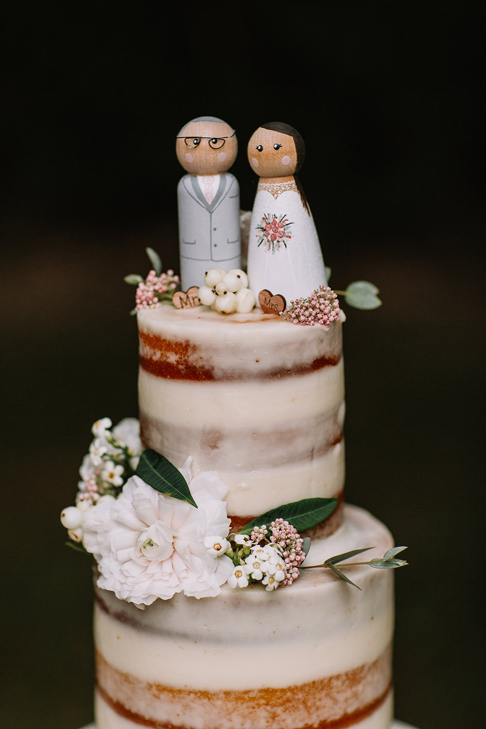 wedding cake with wooden bride and groom cake topper